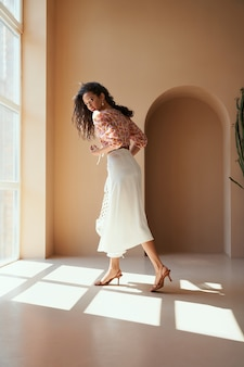 Giovane donna con i capelli lunghi in abiti estivi in posa sulla macchina fotografica