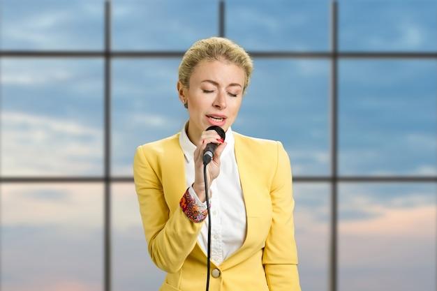 Девушка с закрытыми глазами микрофон. красивая белокурая бизнес-леди, говорящая в микрофон на окне офиса.