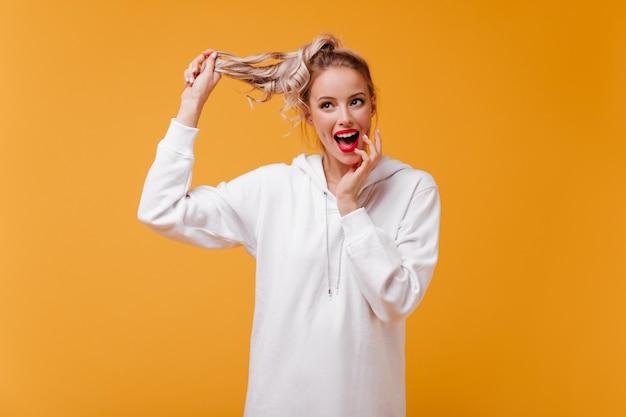 喜んでポーズをとって赤い口紅を持つ若い女性