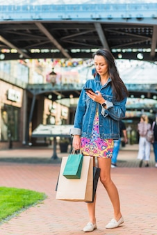 Young lady with shopping bags and mobile phone in mart