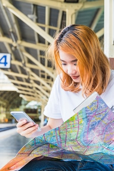 Young lady with smartphone and map