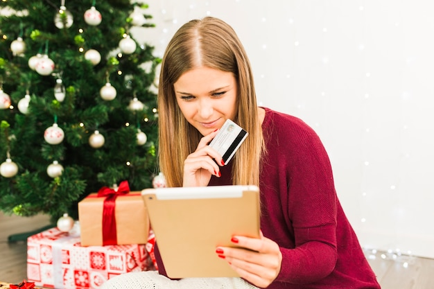 Young lady with tablet and plastic card near gift boxes and christmas tree