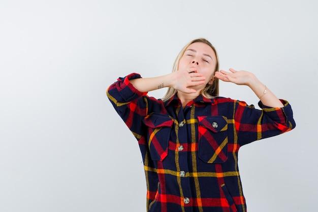 チェックのシャツであくびをして眠そうな若い女性。正面図。