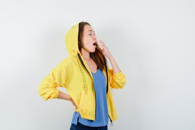 Tシャツ、ジャケット、眠そうに見えるあくびをしている若い女性