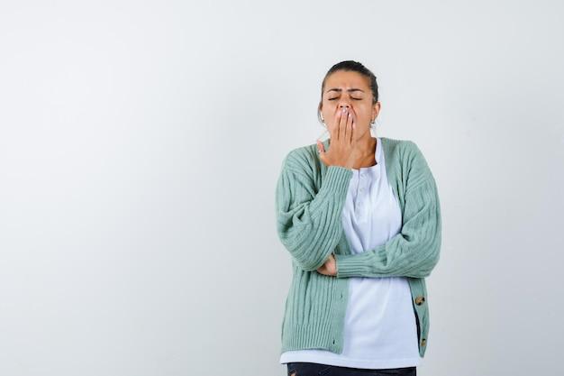 Tシャツ、ジャケットであくびをし、眠そうな若い女性