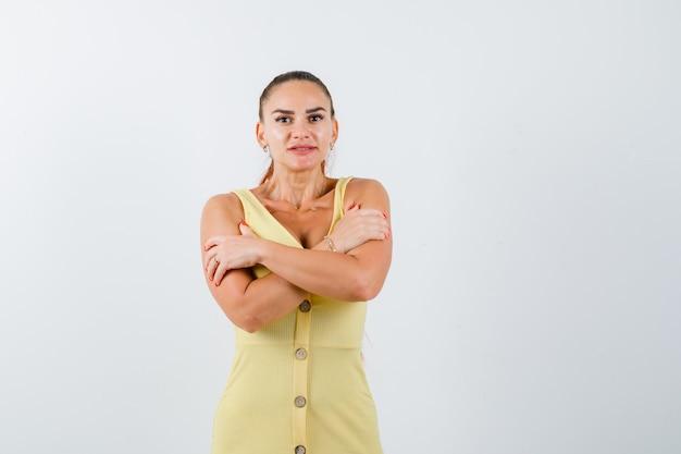 Giovane donna in abito giallo che si abbraccia, si sente freddo e sembra perplessa, vista frontale.
