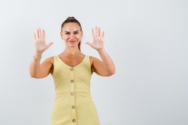 Giovane signora in vestito giallo che mostra gesto di resa e che sembra felice, vista frontale.