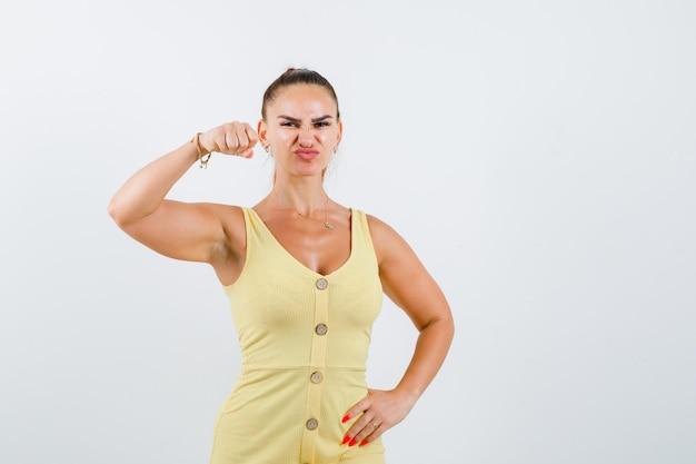 Giovane donna in abito giallo che minaccia di pugno mentre si acciglia e sembra dispettosa, vista frontale.