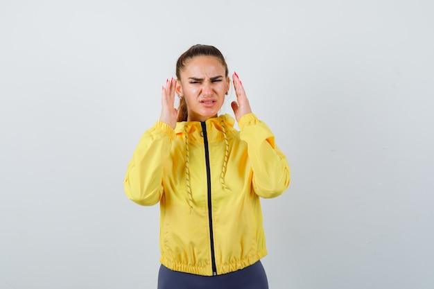 Giovane donna in giacca gialla che tiene le mani vicino al viso e sembra aggressiva, vista frontale.