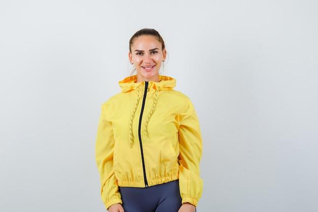 Giovane signora in giacca gialla in posa e guardando gioiosa, vista frontale.