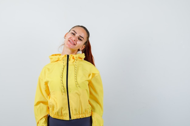 Giovane donna in giacca gialla in posa mentre sembra allegra, vista frontale.