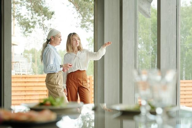 シニア顧客に裏庭の改善を説明しながら手を身振りで示す若い造園家