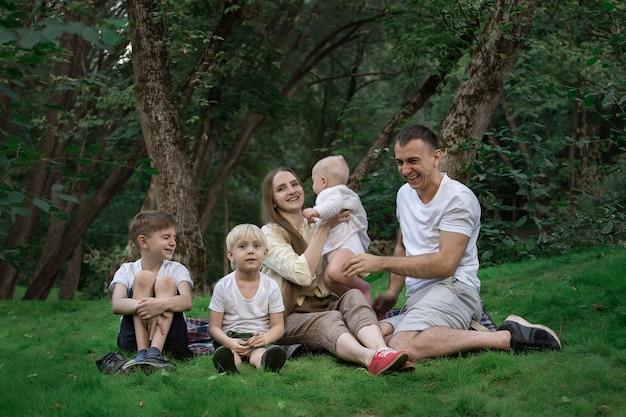 若い大家族は屋外のピクニックを持っています。母父と3人の子供。幸せな家族