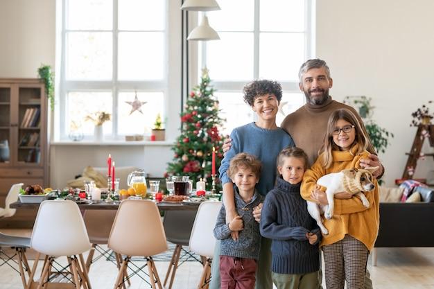 Молодая большая счастливая семья родителей, трех симпатичных детей и их питомца, стоящих в гостиной в день рождества на фоне сервированного праздничного стола