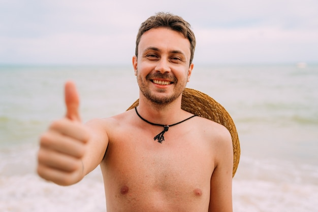 Young latin american man on the beach with a hat and thumb up