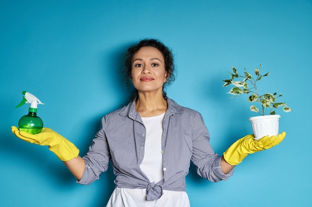 파란색 위에 작은 집 나무와 실내 식물 스프레이와 냄비와 함께 포즈 젊은 라틴 아메리카 여자 정원사