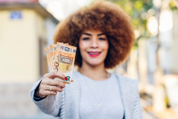 街でお金を持って幸せに笑っている若いラテンアメリカ人女性ヨーロッパのユーロ