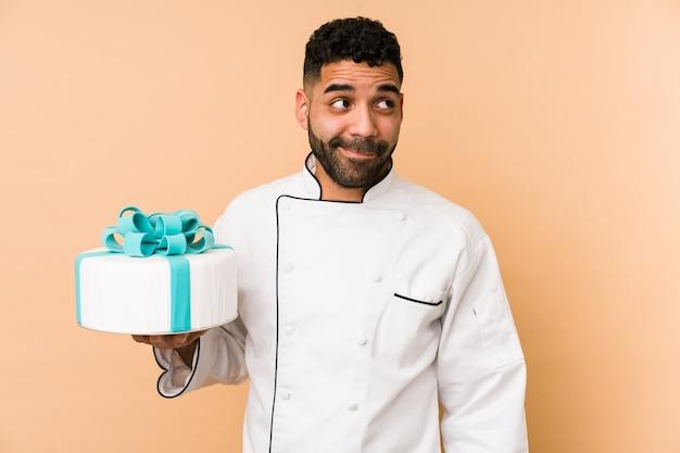 Молодой латинский пекарь, держащий изолированный торт, смущен, чувствует себя сомнительным и неуверенным.