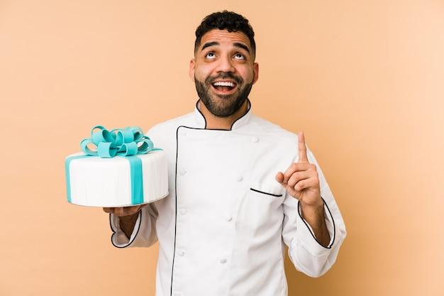 開いた口で逆さまに指している孤立したケーキを保持している若いラテンパン屋の男。