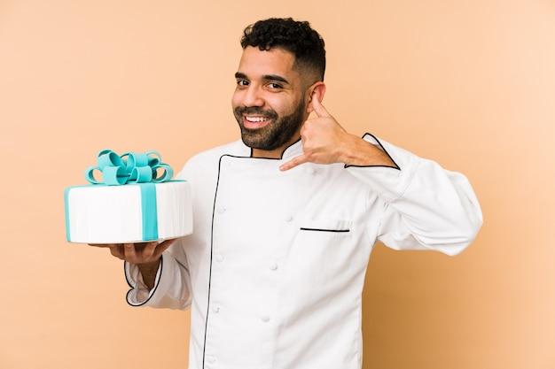 Молодой человек латинского пекаря держит торт, показывая жест вызова пальцами.