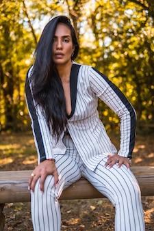 Молодая латинская брюнетка в очень элегантном белом костюме с черными полосками. мода позирует в красивом парке сидя