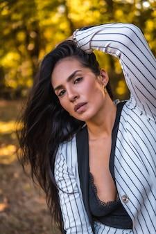 Молодая латинская брюнетка в очень элегантном белом костюме с черными полосками. сидит в красивом парке, портрет гладит волосы
