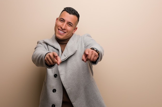 Young latin business man cheerful and smiling pointing to front