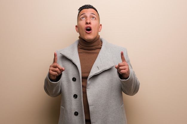 Young latin business man surprised pointing up to show something