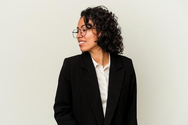 Молодая латинская бизнес-леди, изолированная на белом фоне, смотрит в сторону, улыбаясь, веселая и приятная.