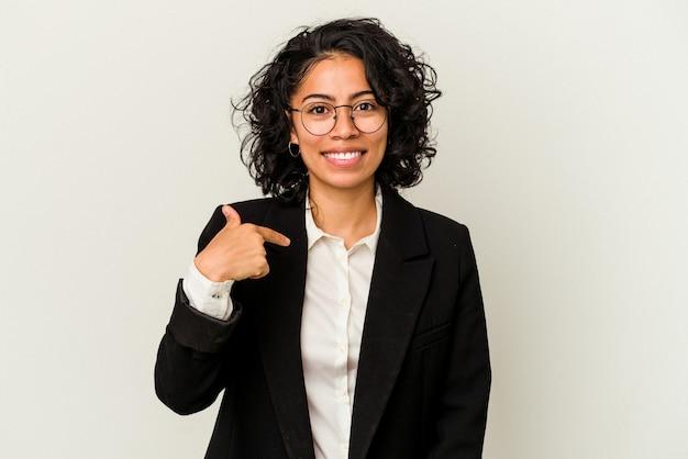 シャツのコピースペースを手で指している白い背景の人に孤立し、誇りと自信を持って若いラテンビジネス女性
