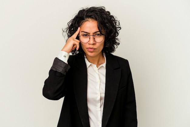指で寺院を指して、思考、タスクに焦点を当てて、白い背景で隔離の若いラテンビジネス女性。