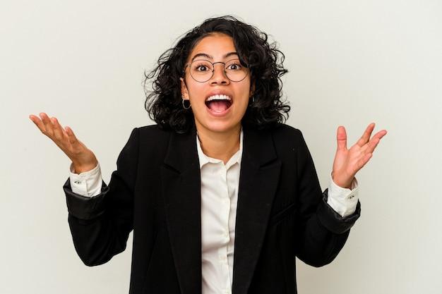 嬉しい驚きを受け取り、興奮し、手を上げる白い背景で隔離の若いラテンビジネス女性。