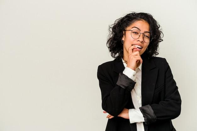 白い背景で隔離の若いラテンビジネス女性は、コピースペースを見ている何かについて考えてリラックスしました。