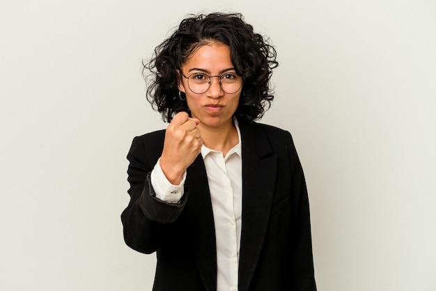 カメラに拳、攻撃的な表情を示す白い背景で隔離の若いラテンビジネス女性。
