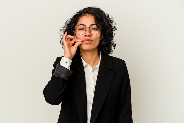 秘密を守る唇に指で白い背景に分離された若いラテン ビジネスの女性。