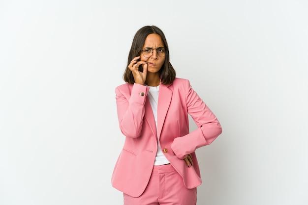 心に手を置いて笑って、幸せの概念、白い壁に孤立した若いラテンビジネス女性。