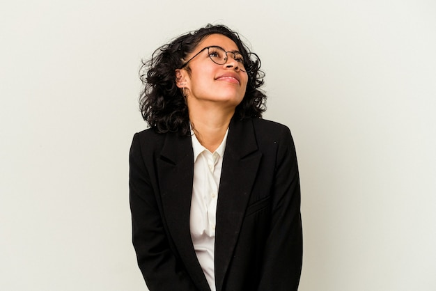 Young latin business woman isolated on white background dreaming of achieving goals and purposes