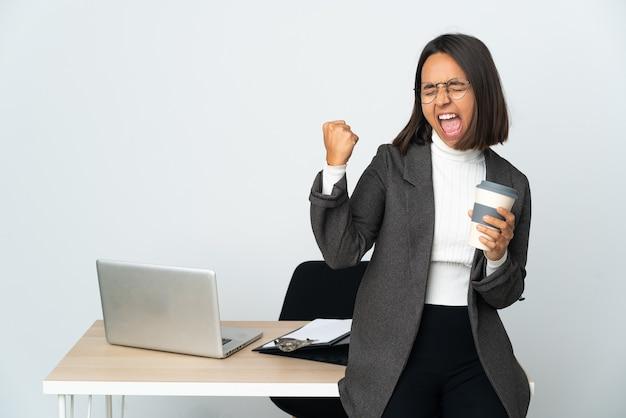 승리를 축하하는 흰색 배경에 고립 된 사무실에서 일하는 젊은 라틴 비즈니스 여자