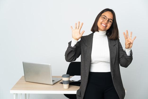 Молодая латинская деловая женщина, работающая в офисе, изолированном на белом фоне, считая девять пальцами