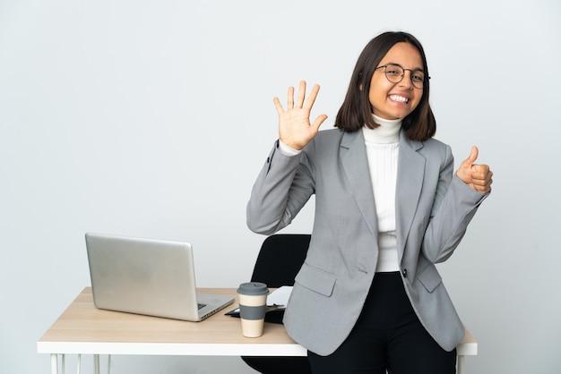 손가락으로 6 세 흰색 배경에 고립 된 사무실에서 일하는 젊은 라틴 비즈니스 여자
