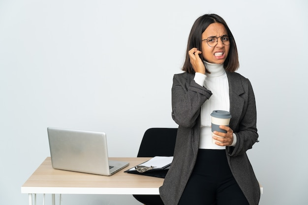 Молодая латинская деловая женщина, работающая в офисе, изолированном на белом фоне, разочарована и закрывает уши