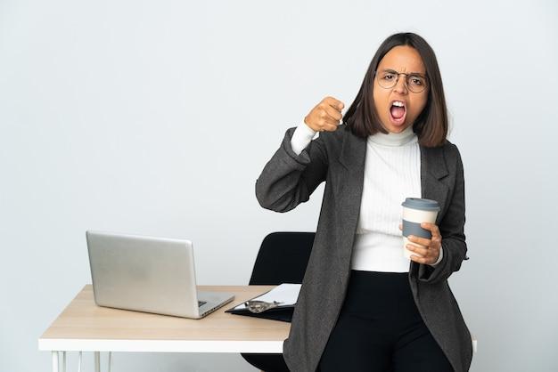 欲求不満と正面を指して白い背景で隔離のオフィスで働く若いラテンビジネス女性