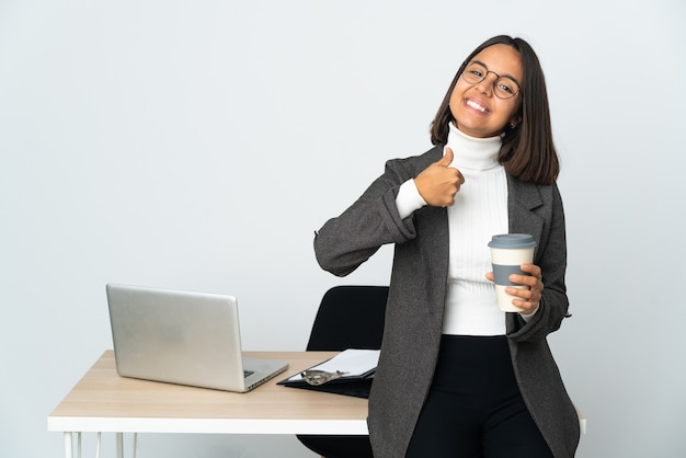 Молодая латинская деловая женщина, работающая в офисе, изолированном на белом фоне, жестом показывает палец вверх
