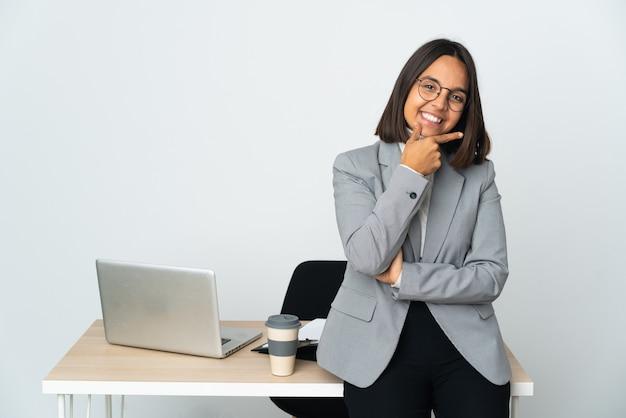 Молодая латинская деловая женщина, работающая в офисе, изолированном на белом фоне, счастлива и улыбается