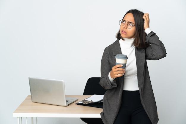머리를 긁적 동안 의심을 갖는 흰색 배경에 고립 된 사무실에서 일하는 젊은 라틴 비즈니스 여자