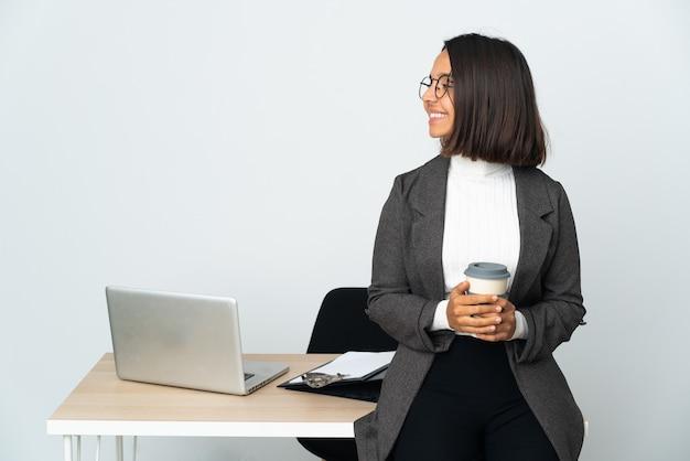 横の位置で白い背景で隔離のオフィスで働く若いラテンビジネス女性