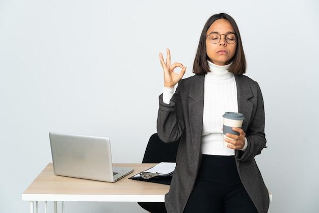 Молодая латинская деловая женщина, работающая в офисе, изолированном на белом фоне в позе дзен