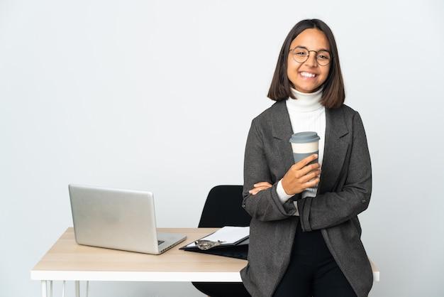 Молодая латинская деловая женщина, работающая в офисе, изолированном на белом фоне, смеясь