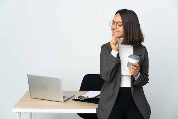 Молодая латинская деловая женщина, работающая в офисе, изолированном на белом фоне, смотрит в сторону и улыбается