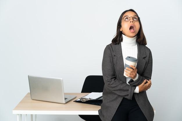 Молодая латинская деловая женщина, работающая в офисе, изолированном на белом фоне, смотрит вверх и с удивленным выражением лица